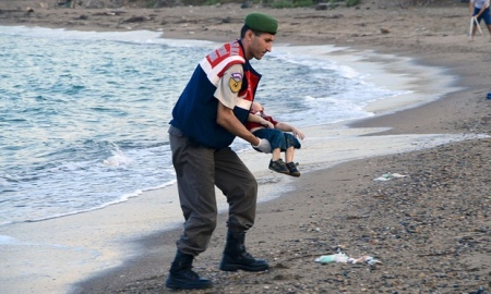 A Turkish police officer carries a young boy who drowned in a failed attempt to sail to the Greek island of Kos. Photograph: Reuters